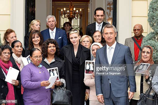 Princess Charlene of Monaco and Philippe Narmino pose with Monegasque citizens at the Monaco Red Cross headquarters on November 17 2015 in Monaco...