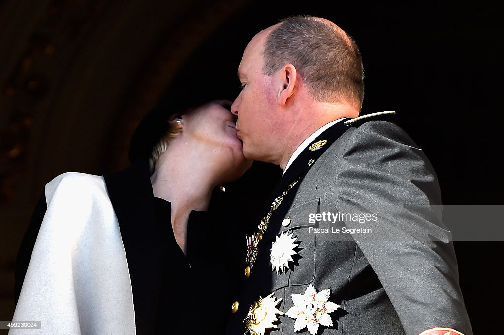 Princess Charlene of Monaco and Prince Albert II of Monaco kiss from the palace's balcony during the National Day Parade as part of Monaco National Day Celebrations on November 19, 2014 in Monaco, Monaco.