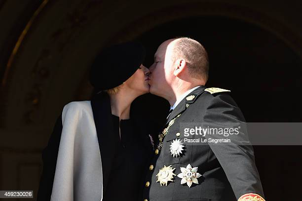 Princess Charlene of Monaco and Prince Albert II of Monaco kiss from the palace's balcony during the National Day Parade as part of Monaco National...