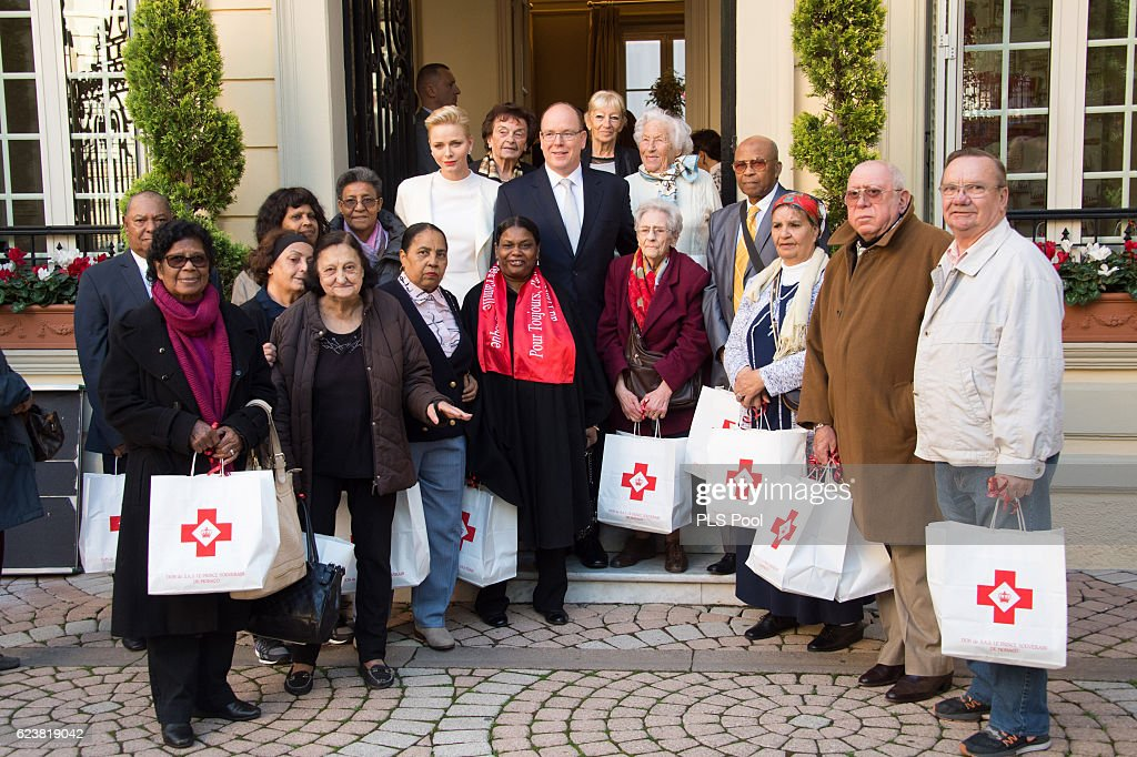 Princess Charlene of Monaco and Prince Albert II of Monaco pose with refugees during the Parcels Distribution At Monaco Red Cross Headquarters on November 17, 2016 in Monaco, Monaco.