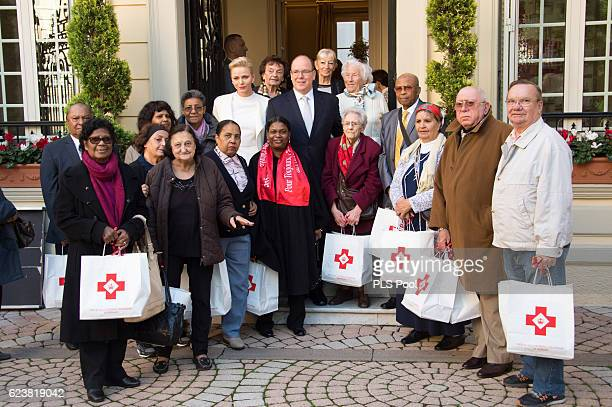 Princess Charlene of Monaco and Prince Albert II of Monaco pose with refugees during the Parcels Distribution At Monaco Red Cross Headquarters on...