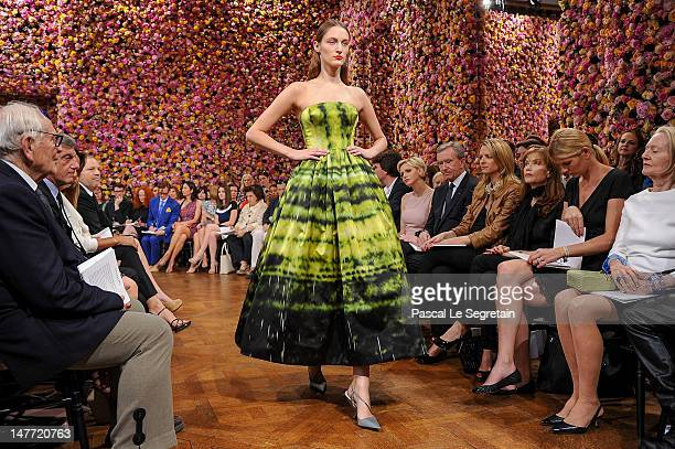 Princess Charlene of Monaco, Bernard Arnault, Delphine Arnault, Isabelle Huppert and guests watch a model as she walks the runway during the...
