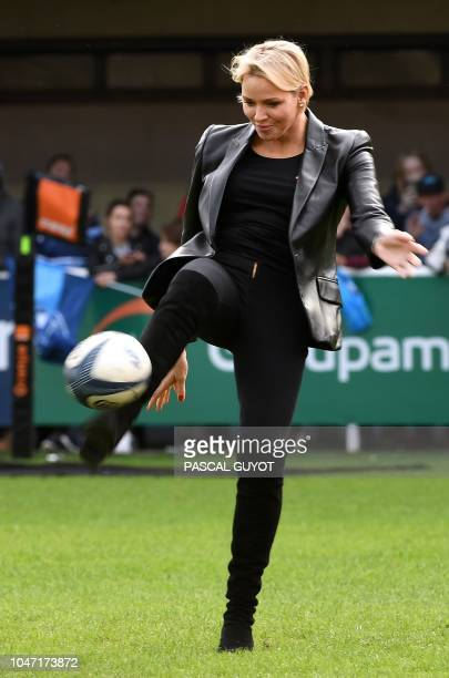 Princess Charlene of Monaco kicks a ball before attending the French Top 14 rugby union match between Montpellier and Toulon on October 7 2018 at the...