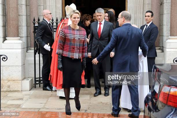 Princess Charlene of Monaco looks on next to Prince Albert II of Monaco as they leave the Monaco Cathedral during Sainte Devote Celebrations in...