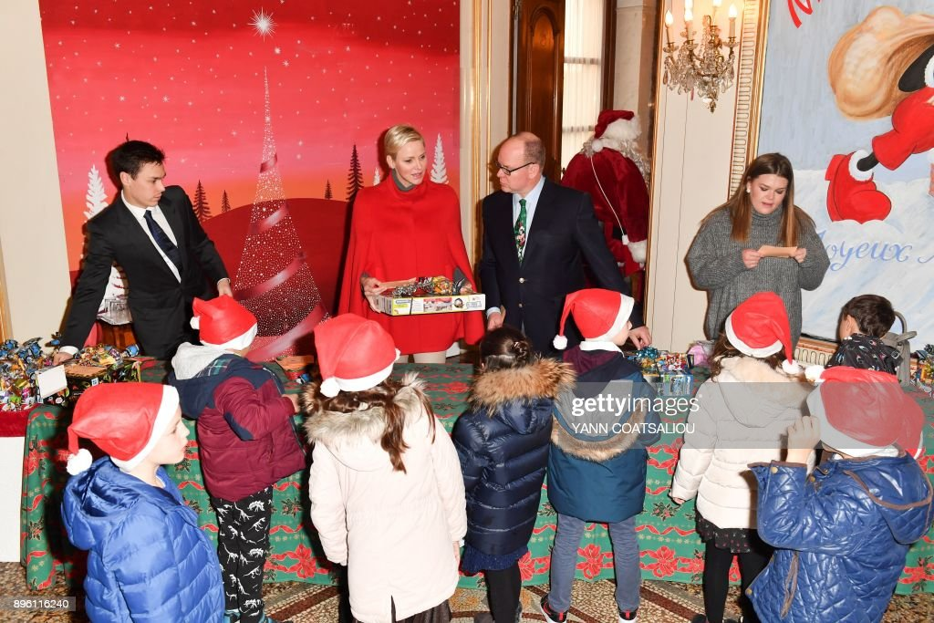Princess Charlene of Monaco (2nd L), Prince Albert II of Monaco (2ns R), his nephew Daniel Ducruet (L) and niece Camille Gotlieb (R) deliver gifts during the Children's Christmas ceremony at the Monaco Palace on December 20, 2017. /