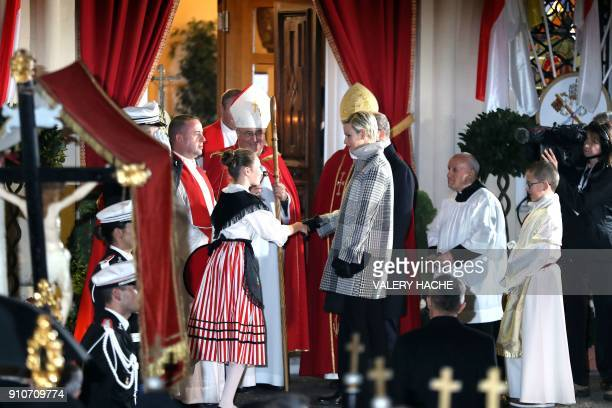 Princess Charlene of Monaco shakes hands with a girl as she arrives on January 26 2018 in Monaco during the SainteDevote procession Sainte devote is...