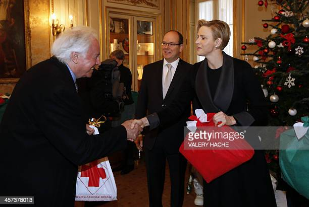 Princess Charlene of Monaco shakes hands with a resident of Monaco as she gives Christmas presents with Prince's Albert II on December 17 in Monaco...