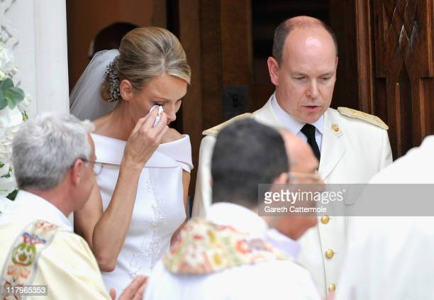 Princess Charlene of Monaco wipes away a tear as she and Prince Albert II of Monaco leave Sainte Devote church after their religious wedding ceremony...