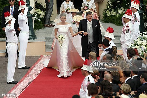 Princess Charlene on her father Mike Wittstock's arm walks along a red carpet from the Carabiniers Barracks to the altar for the wedding ceremony in...