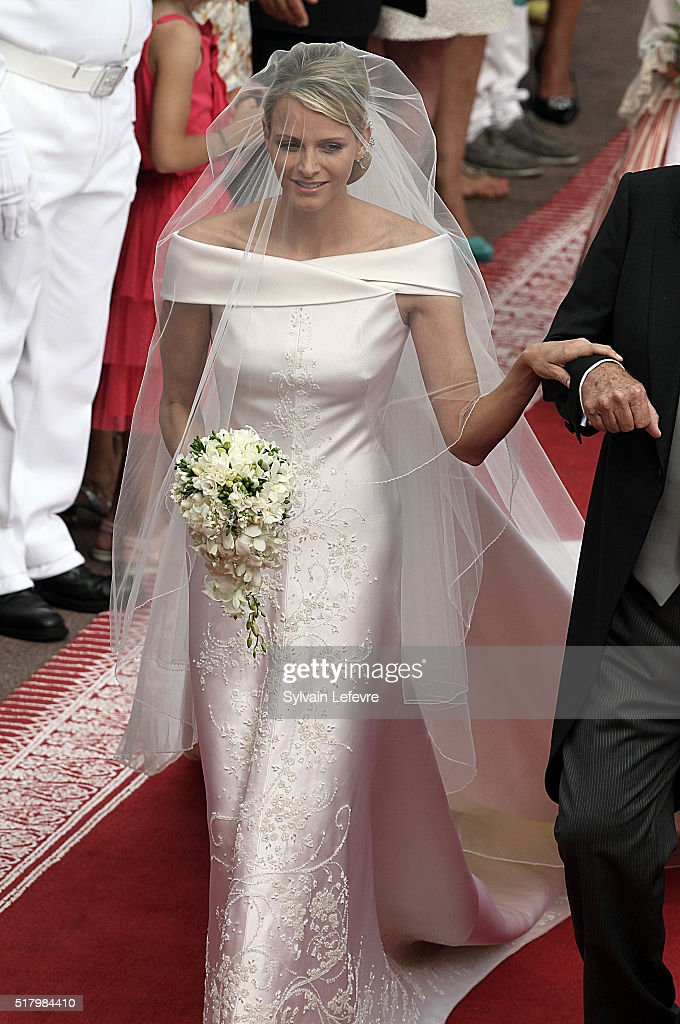 Princess Charlene (L), on her father Mike Wittstock's arm, walks along a red carpet from the Carabiniers Barracks to the altar for the wedding ceremony in the Main Courtyard of the Prince's Palace in Monaco, 02 July 2011. Photo by Sylvain Lefevre/Getty Images
