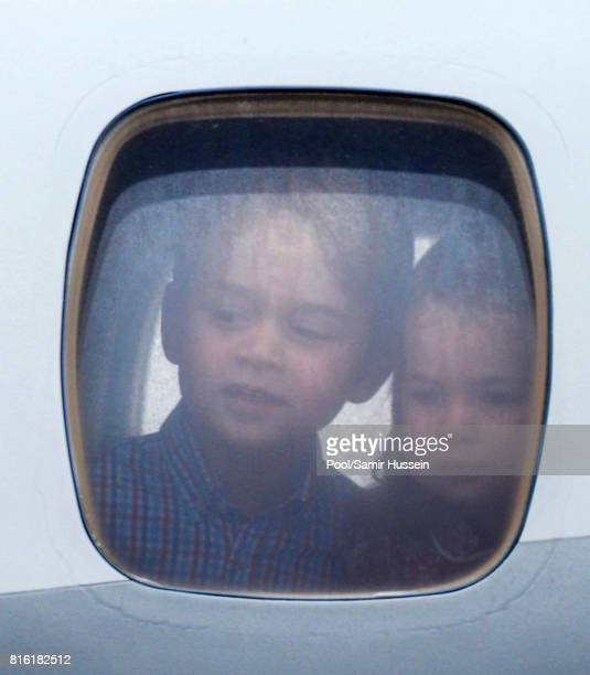Princess Charlotte of Cambridge and Prince George of Cambridge look out of the window of the plane as they arrive at Warsaw airport during an...