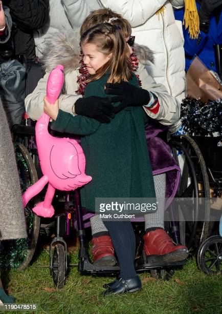 Princess Charlotte of Cambridge gets a hug from a member of the public at the Christmas Day Church service at Church of St Mary Magdalene on the...