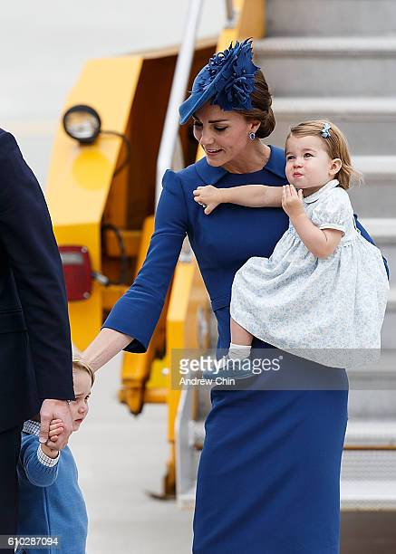 Princess Charlotte of Cambridge holds on to Catherine Duchess of Cambridge's maple leaf broach upon their arrival at 443 Maritime Helicopter Squadron...