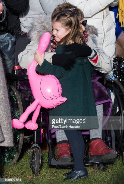 Princess Charlotte of Cambridge is given a hug by a wellwisher as she attends the Christmas Day Church service at Church of St Mary Magdalene on the...