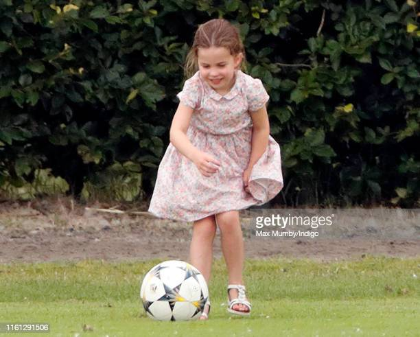 Princess Charlotte of Cambridge plays football as she attends the King Power Royal Charity Polo Match, in which Prince William, Duke of Cambridge and...
