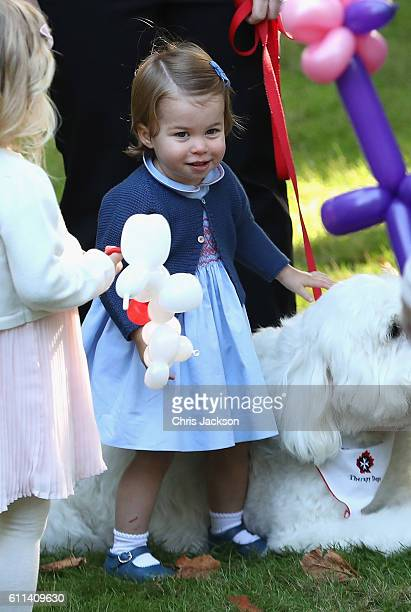 Princess Charlotte of Cambridge plays with a dog named Moose at a children's party for Military families during the Royal Tour of Canada on September...