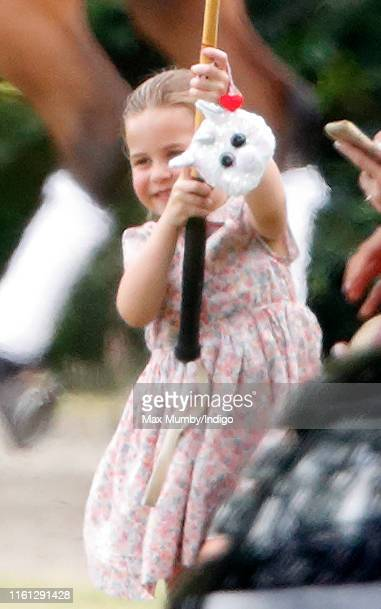 Princess Charlotte of Cambridge plays with a polo mallet as she attends the King Power Royal Charity Polo Match, in which Prince William, Duke of...