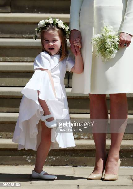 Princess Charlotte of Cambridge stands on the steps holding the hand of her mother Britain's Catherine Duchess of Cambridge after attending the...