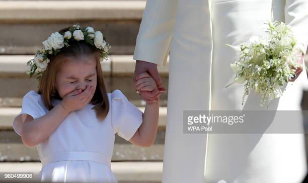 Princess Charlotte of Cambridge stands on the steps with her mother Catherine, Duchess of Cambridge after the wedding of Prince Harry and Ms. Meghan...