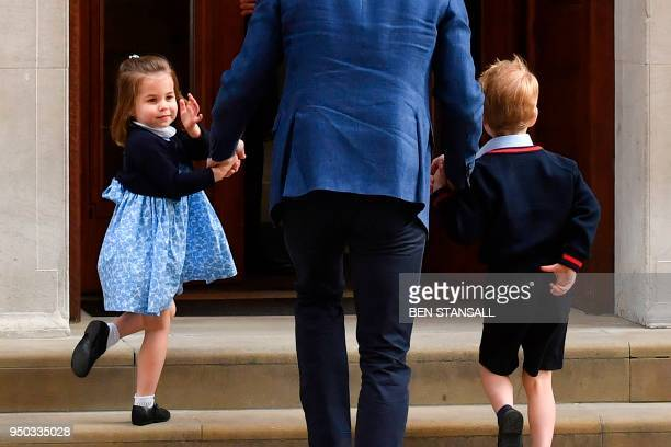 Princess Charlotte of Cambridge turns to wave at the media as she is lead in with her brother Prince George of Cambridge by their father Britain's...
