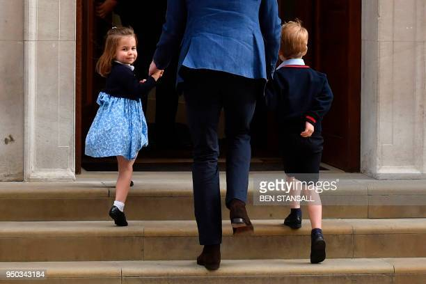 TOPSHOT Princess Charlotte of Cambridge turns to wave at the media as she is led in with her brother Prince George of Cambridge by their father...