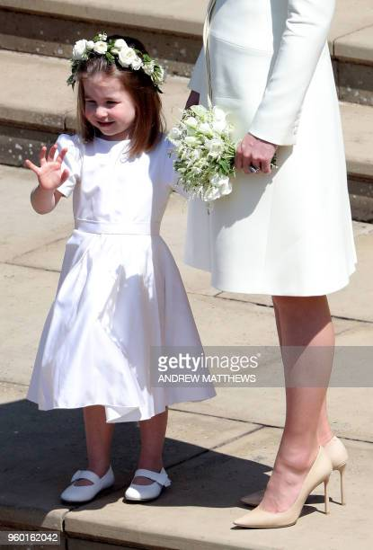 Princess Charlotte of Cambridge waves after attending the wedding ceremony of Britain's Prince Harry Duke of Sussex and US actress Meghan Markle at...