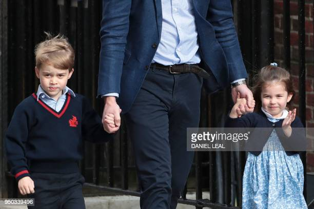 Princess Charlotte of Cambridge waves at the media as she is led in with her brother Prince George of Cambridge by their father Britain's Prince...