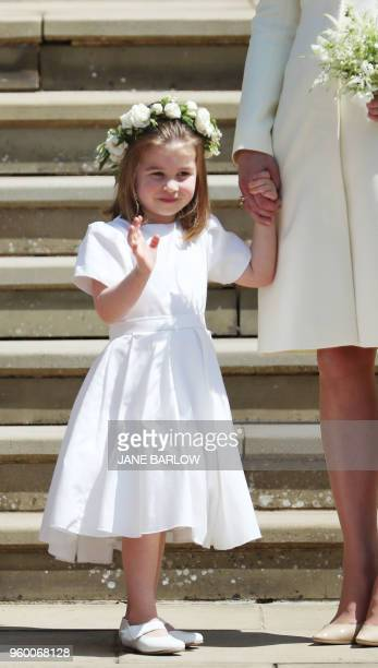 Princess Charlotte of Cambridge waves holding the hand of her mother Britain's Catherine Duchess of Cambridge after attending the wedding ceremony of...