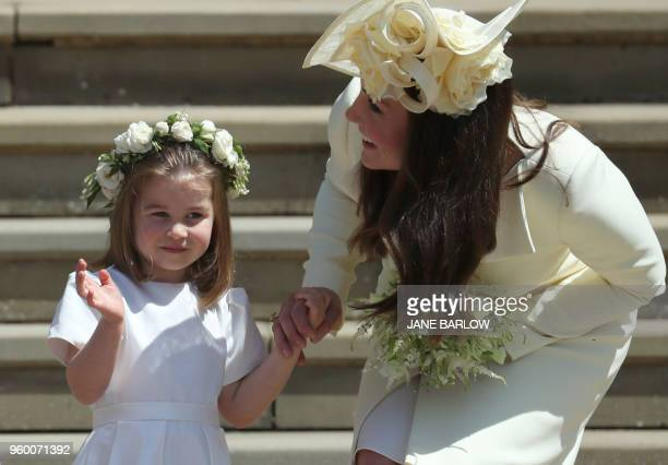 TOPSHOT Princess Charlotte waves by her mother Britain's Catherine Duchess of Cambridge after attending the wedding ceremony of Britain's Prince...