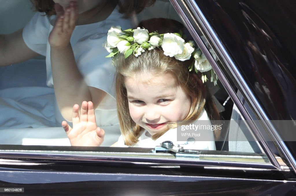 Princess Charlotte waves to the crowd as she rides in a car to the wedding of Prince Harry and Meghan Markle at St George's Chapel in Windsor Castle on May 19, 2018 in Windsor, England.