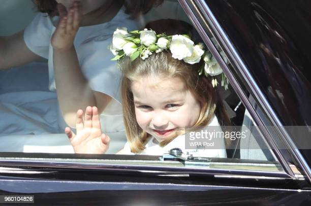 Princess Charlotte waves to the crowd as she rides in a car to the wedding of Prince Harry and Meghan Markle at St George's Chapel in Windsor Castle...