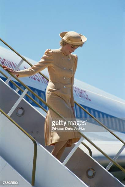 Princess Diana arriving at Melbourne airport wearing a beige coat dress and matching hat October 1985