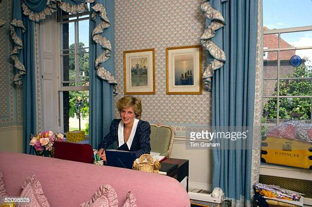 Princess Diana At Her Desk In Her Sitting Room At Home In Kensington Palace, London. Beside Her Is Her School Tuckbox With The Name D.spencer.