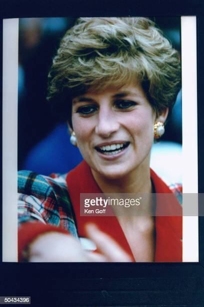Princess Diana clad in a wool red green plaid shirtwaist dress holding a small bouquet of flowers during her walking tour