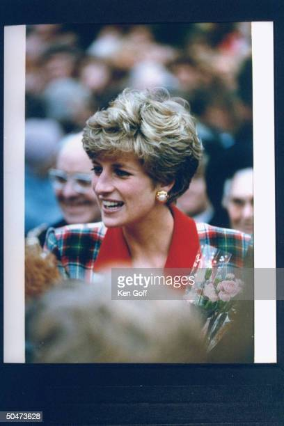 Princess Diana clad in a wool red green plaid shirtwaist dress holding a small bouquet of flowers during her walking tour North England