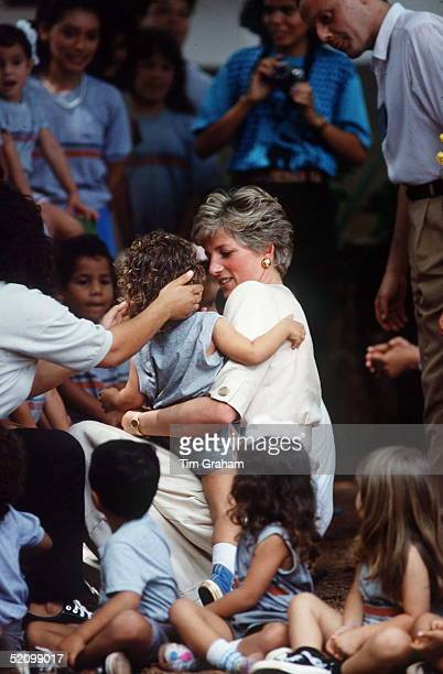 Princess Diana Holding A Little Girl While Visiting An Elementary School In Carajas During Her Official Tour Of Brazil