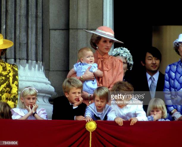 Princess Diana holds her son Prince Harry as she watches the Trooping of the Colour from the balcony of Buckingham Palace, London, June 1985. On the...