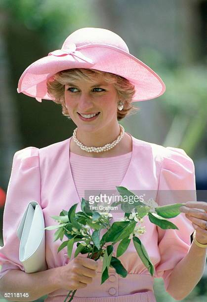 Princess Diana In Sicily Holding Orange Blossom Flowers Wearing An Outfit Designed By Fashion Designer Catherine Walker And A Hat By Milliner John...