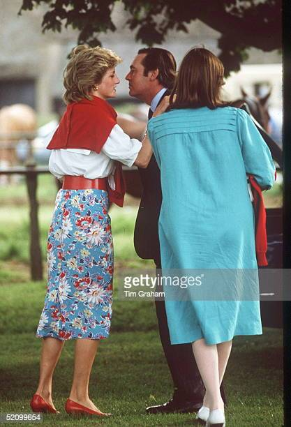 Princess Diana Kissing Sam Vestey On Meeting Him And His Wife During A Polo Match At Cirencester Polo Club. Diana Is Wearing A Blue Flowered Skirt...
