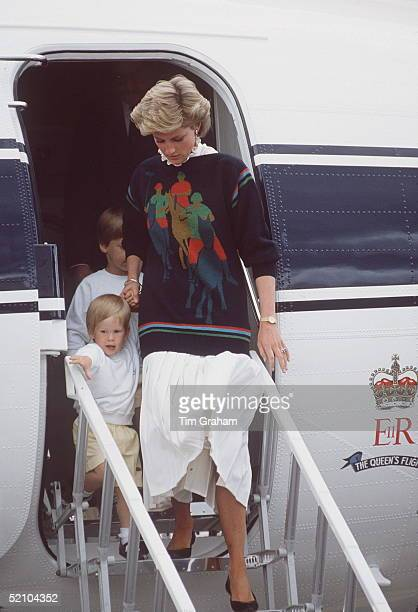 Princess Diana Leaving A Plane At Aberdeen Airport With Prince Harry At The Start Of Their Annual Holiday In Scotland Her Jumper Has A Motif Of A...