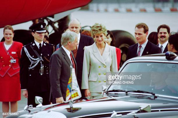 Princess Diana makes a funny face after Hong Kong Governor Chris Patten shows her the direction of the press group covering her arrival on April 21...