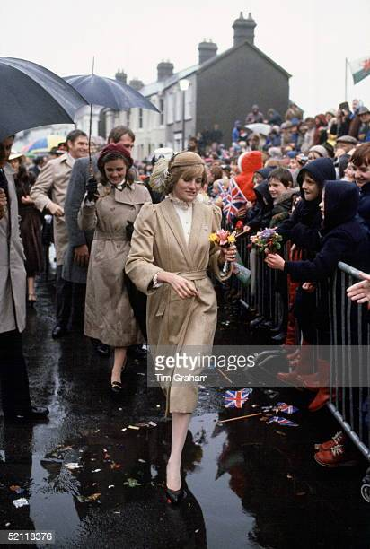 Princess Diana On Her First Official Visit To Wales Walking Through Puddles And Refusing To Shelter Under An Umbrella. Behind Is Her Lady-in-waiting...
