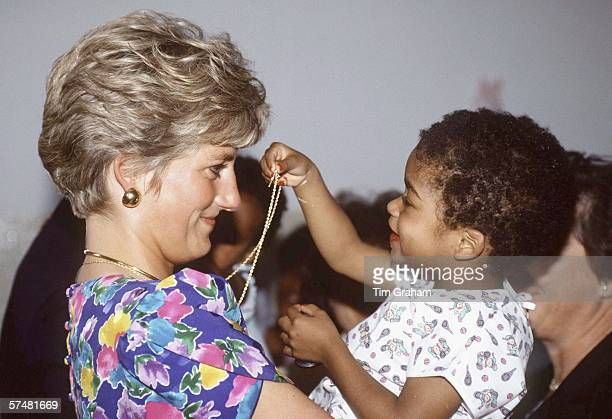 Princess Diana Princess of Wales is seen cuddling a child during a visit to a hostel for abandoned children many of whom are HIV positive or suffer...