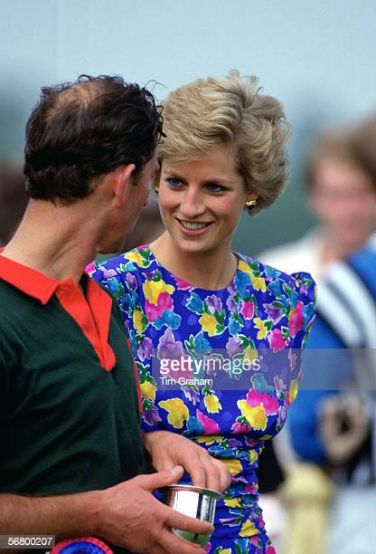 Princess Diana, Princess of Wales presents Prince Charles, Prince of Wales with a trophy after competing at the Hola Cup Polo, Windsor.