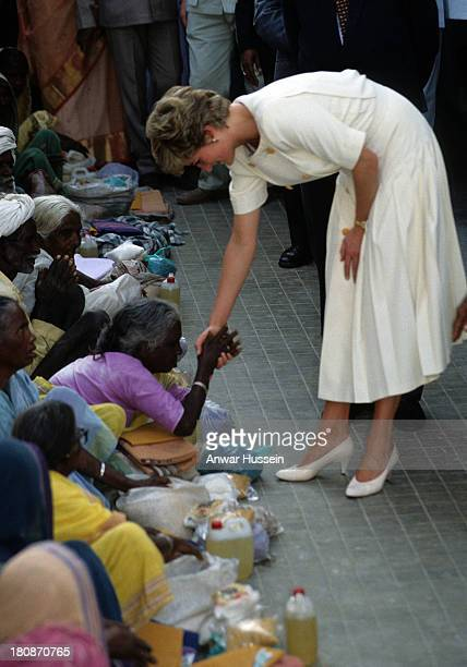 Princess Diana Princess of Wales wearing a Catherine Walker dress shakes hands with an 'untouchable' India's lowest caste at the Mianpur Old Age...
