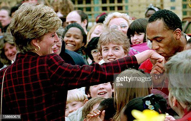 Princess Diana receives a kiss on the hand from trainee electrician Danny Walters during a walk in Southwark South London 10 March 1993