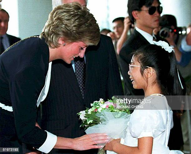 Princess Diana receives flowers from Stella Chan a daughter of a cancer patient during a tour of a local hospital 22 April in Hong Kong The Princess...