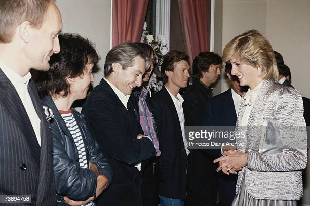 Princess Diana shares a joke with Rolling Stones drummer Charlie Watts after a rock concert at the Albert Hall, London, September 1983. Guitarist...