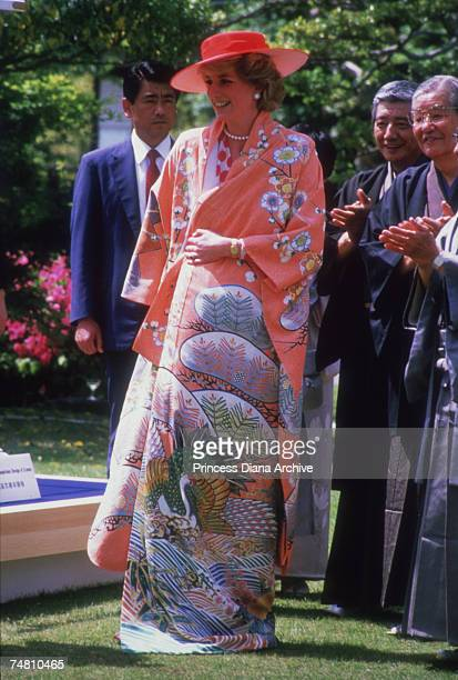 Princess Diana trying on a kimono she received as a gift at Nijo Castle, Kyoto, during an official visit to Japan, May 1986.
