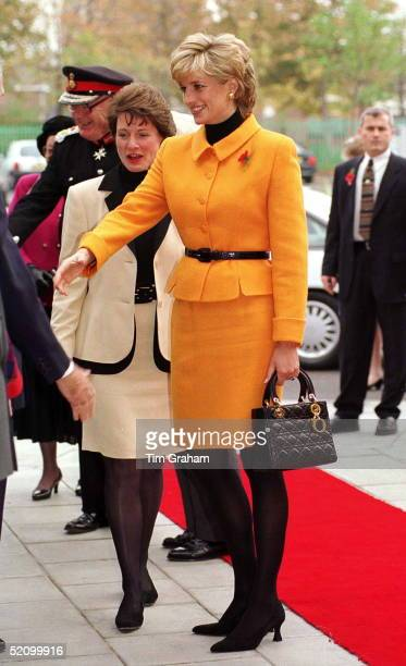 Princess Diana Visiting Liverpool. Diana Is Wearing A Bright Orange Suit Designed By Versace And She Is Carrying A Dior Handbag.